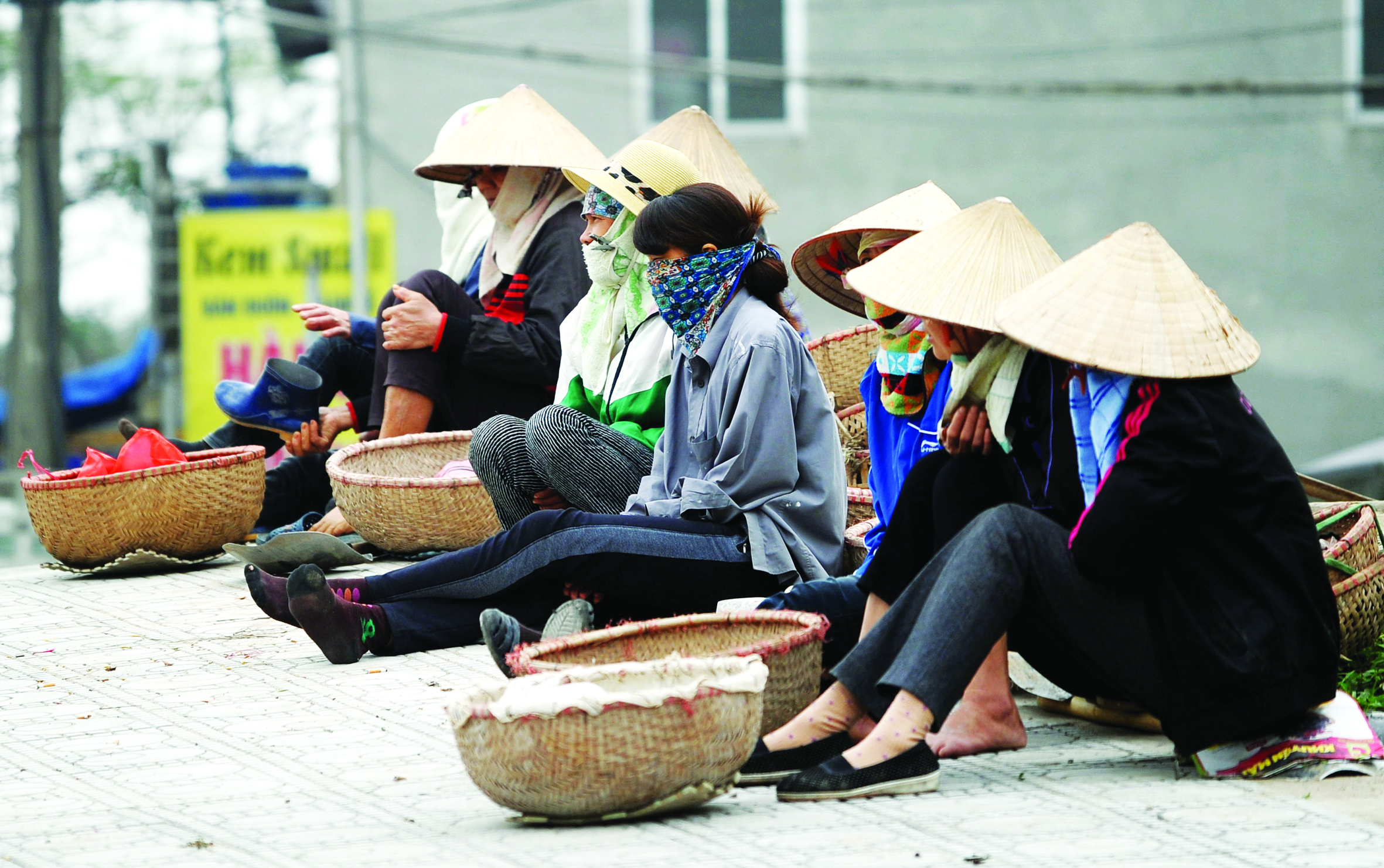 Day-labourers sit waiting for employers to hire them for the day, along a road in Hanoi on March 28, 2016. Vietnam's economy slowed in the first quarter of 2016, official figures shows on March 25, hampered by low oil prices and an ongoing drought that has hit the agricultural sector hard.  / AFP PHOTO / HOANG DINH NAM