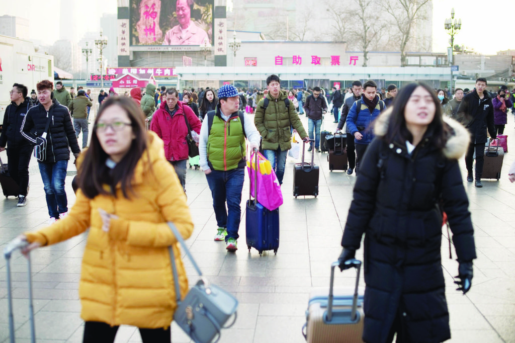 "Passengers arrive at the train station as they prepare to travel to their hometowns for the ""Spring Festival"" or Lunar New Year on January 24, 2017 at Beijing Railway Station. The huge movement of Chinese travelling home to spend the Lunar New Year with their families is often described as the world's largest human migration and overcrowded planes, trains and automobiles are the norm. / AFP PHOTO / NICOLAS ASFOURI"