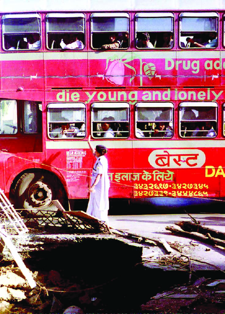 A double-decker bus passes 16 March 1993 the crater of a 12 March bomb blast, one of a series of bombs that rocked this western port city, India. More than 300 people were killed in the blasts, which a senior police official has blamed on Bombay's criminal underworld. / AFP PHOTO / DOUGLAS E. CURRAN